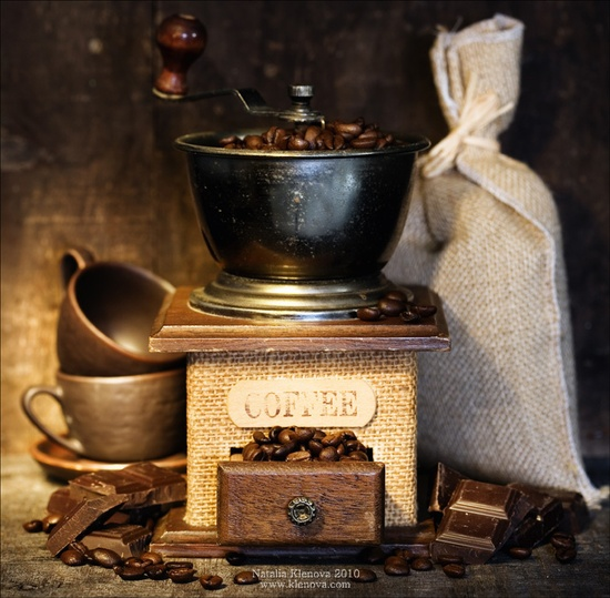 Still life with Antique coffee grinder, burlap sack, coffee cups and chocolate on  rustic table